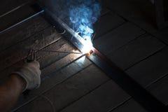 Arbeitskraft mit Schutzhandschuhschweißensmetall und -funken Lizenzfreies Stockfoto