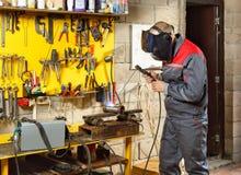 Arbeitskraft mit Schutzmaskeschweißen Stockbild