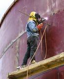 Arbeitskraft mit Schutzmaskeschweißensmetall und -funken Stockfoto