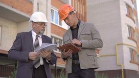 Arbeitskraft mit zwei Geschäften im Sturzhelm besprechend, unter Verwendung der nahen Gestalt der Tablette 4K stock video