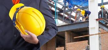 Arbeitskraft oder Ingenieur, die im Handgelben Sturzhelm halten Lizenzfreie Stockfotos
