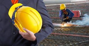 Arbeitskraft oder Ingenieur, die im Handgelben Sturzhelm halten Stockbild