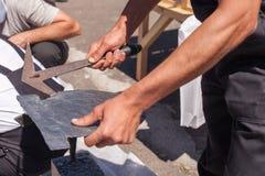 Arbeitskraft produziert Deckungsschiefer unter Verwendung eines Schieferhammers lizenzfreies stockfoto