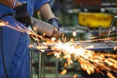 Arbeitskraft reibend Stahl durch elektrische Schleifmaschine Lizenzfreie Stockfotografie