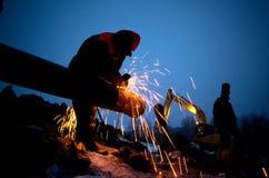 Arbeitskraft reibt ein Rohr Stockfotografie