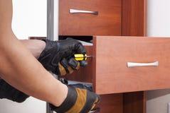 Arbeitskraft repariert Möbel Stockfotografie