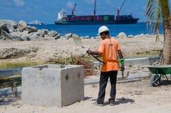 Arbeitskraft säubert Schaufel, indem er sie auf Stein klopft Stockfotografie