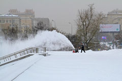 Arbeitskraft säubert Schnee von den Bürgersteigen mit Schneekanone Stockbild