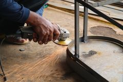 Arbeitskraft Sawingmetall mit einem Schleifer, Arbeitskraft, die den Stahl, Version 14 schweißt stockfotografie
