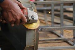 Arbeitskraft Sawingmetall mit einem Schleifer, Arbeitskraft, die den Stahl, Version 16 schweißt Stockfoto