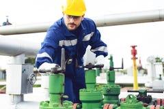 Arbeitskraft schließt das Ventil auf der Ölpipeline stockbilder