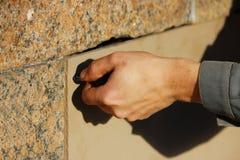 Arbeitskraft schließt die Kellerfenster mit Sperrholz im Gatchina-Palast und verdreht Schrauben ein Schraubenzieher Lizenzfreie Stockfotografie