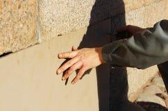 Arbeitskraft schließt die Kellerfenster mit Sperrholz im Gatchina-Palast und verdreht Schrauben ein Schraubenzieher Lizenzfreies Stockfoto