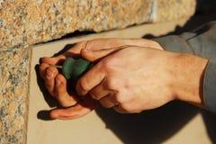 Arbeitskraft schließt die Kellerfenster mit Sperrholz im Gatchina-Palast und verdreht Schrauben ein Schraubenzieher Lizenzfreie Stockbilder