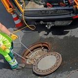 Arbeitskraft schließt einen Kanaldeckel in der Straße stockbilder