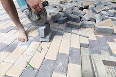 Arbeitskraft schneidet Pflastersteine für das Legen auf den Bürgersteig Stockfotografie