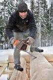 Arbeitskraft schneidet seitliche Hauptnuten des Klotzes unter Verwendung der Kettensäge Lizenzfreies Stockbild