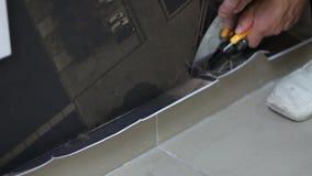 Arbeitskraft schneidet Tapete nahe dem Boden, nachdem er tapeziert hat stock video footage