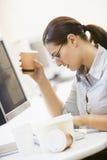 Arbeitskraft am Schreibtisch mit Kaffee Stockfotos