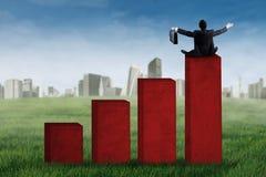 Arbeitskraft sitzt auf dem Finanzdiagramm Lizenzfreies Stockbild