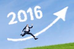 Arbeitskraft springt mit Zahlen 2016 und aufwärts Pfeil im Himmel Lizenzfreies Stockfoto