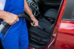 Arbeitskraft-staubsaugendes Auto mit Staubsauger Lizenzfreie Stockfotos