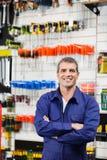 Arbeitskraft-stehende Arme gekreuzt im Hardware-Shop lizenzfreie stockfotografie