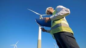 Arbeitskraft steht nahe einer Windkraftanlage und liest Papier auf einem Klemmbrett Auswechselbares electririty, grünes Energieko stock video