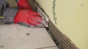 Arbeitskraft stellt kleine Fliesen auf der Wand in der Küche ein Seine Hände setzen die Fliese auf den Kleber stedikam Schießen stock footage