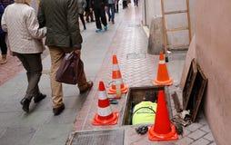 Arbeitskraft am Straßenabwasserkanal Stockfotos