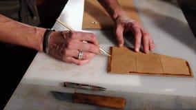 Arbeitskraft trägt Kleber auf lederne Details von Taschen, während der Verarbeitung auf stock footage
