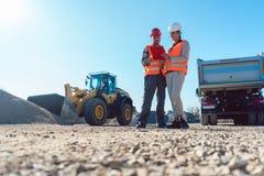 Arbeitskraft und Ingenieur auf BodenbewegungsBaustelleplanung Lizenzfreie Stockbilder