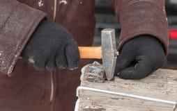 Arbeitskraft verbiegt Metall mit einem Hammer stockfoto
