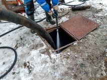 Arbeitskraft, welche die Klärgrube mit Wasser nachdem dem Leeren durch Abwasserreinigermaschinerie säubert lizenzfreies stockbild