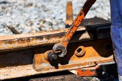 Arbeitskraft zieht das skrew in den Bahn- oder Trambahnen fest lizenzfreie stockfotografie