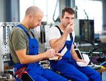 Arbeitskraft zwei in der Fabrik haben einen Bruch Stockfotos