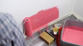 Arbeitskraftanstreicher, der die Wand mit rosa Farbe malt Gebäude stock footage