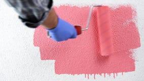 Arbeitskraftanstreicher, der die Wand mit rosa Farbe malt Gebäude stock video footage