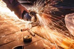Arbeitskraftausschnittmetall mit Schleifer Funkt beim Reiben des Eisens Stockbild