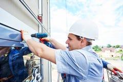 Arbeitskrafterbauer, der Glasfenster auf Fassade installiert Stockbild