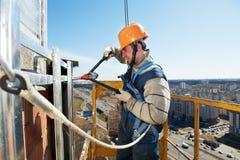 Arbeitskrafterbauer am Fassadeflieseeinbau Lizenzfreies Stockfoto