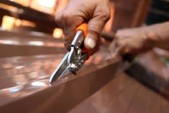 Arbeitskraftgebrauch scissors, um die Blechtafel für die Überdachung zu schneiden Lizenzfreies Stockfoto