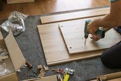 Arbeitskraftgebrauchselektroschrauber, zum von Möbeln zu installieren stockfotos