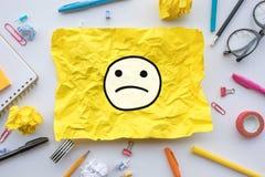 Arbeitskraftgefühlkonzepte mit Emoticongesicht auf dem gelben Papier zerknittert Geschäftsideenlösung und menschliche Leistung stockfotografie
