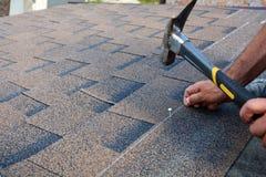 Arbeitskrafthände, die Bitumendachschindeln installieren Arbeitskraft-Hammer in den Nägeln auf dem Dach Roofer hämmert einen Nage stockfotos