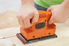 Arbeitskrafthände mit Maschine der elektrischen Sandpapierschleifmaschine Lizenzfreies Stockbild