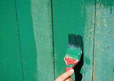 Arbeitskrafthand mit der Bürste, die alte Holzoberfläche malt Malen Sie hölzerne alte Tür Stockfotografie