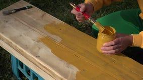 Arbeitskraftmaler übergibt Malereiholzoberfläche mit Malerpinsel in der gelben Farbe nahaufnahme 4K stock video