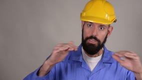 Arbeitskraftmann im gelben Sturzhelm erklären etwas und zeigen O.K.geste auf grauem Hintergrund stock video