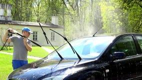 Arbeitskraftmann mit dem Hochdruckwasserstrahlwerkzeug, das sein Autoautomobil wäscht stock footage